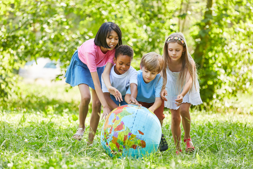 Multicultural group of kids rolls globe ball in teamwork in the park