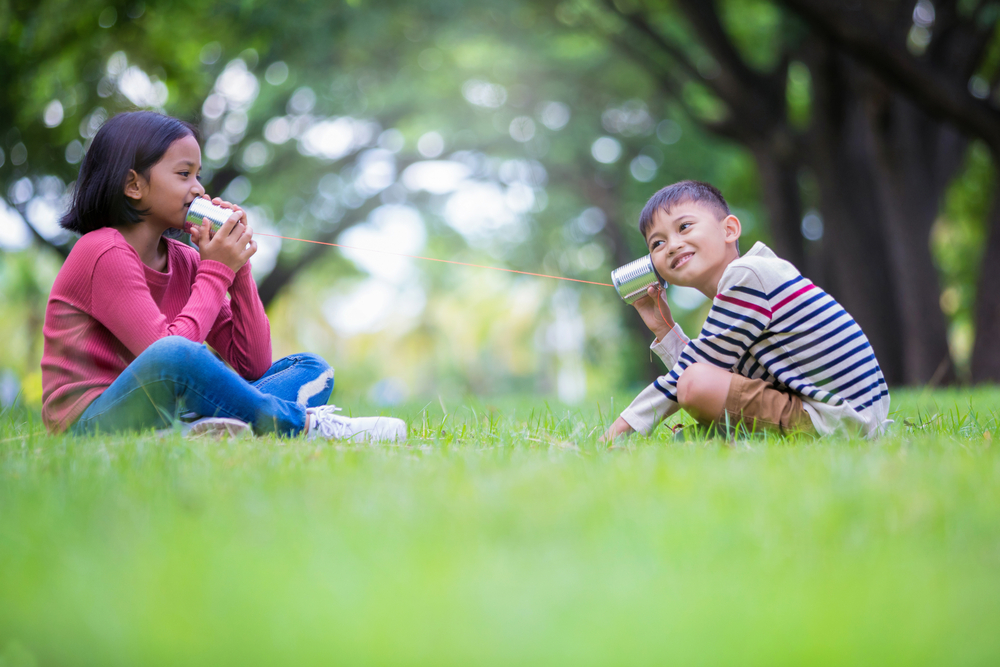 asian boy and girl playing with can as a phone in the park