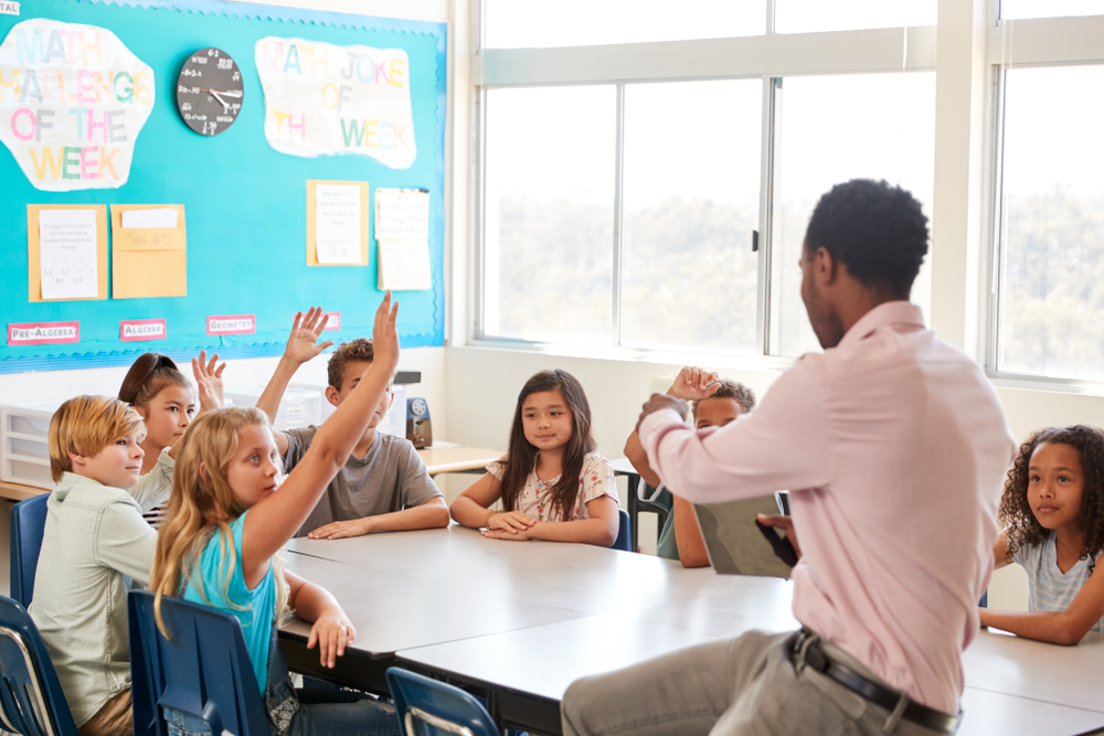 Kids raising hands to answer in an elementary school lesson