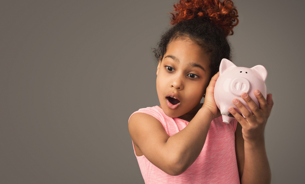 Little black girl with piggy bank, studio shot, copy space