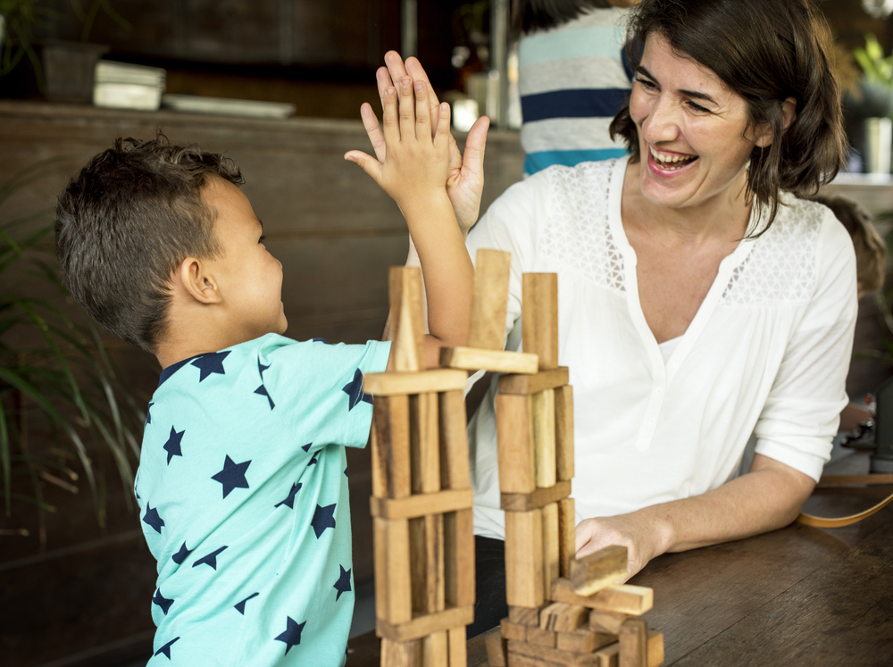 Little Boy Playing Wooden Block Toy with Teacher